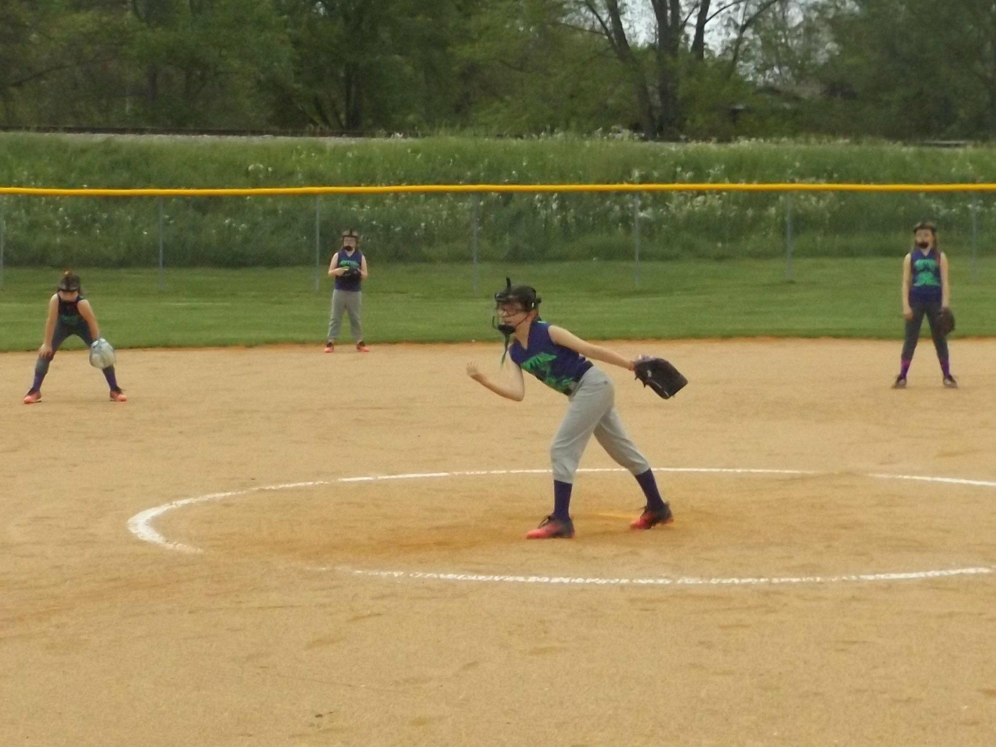 young player pitching softball ball